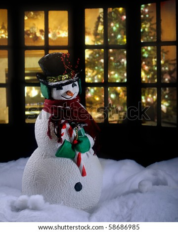 A Christmas snowman in the snow at night with a living room decorated for the holidays seen through a silhouetted window behind him.  Intentionally dark for nighttime lighting.