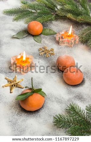 Stock Photo A Christmas still life. Orange tangerines, orange candles, fir branches on the table covered with frost.
