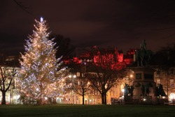 A Christmas tree in Charlotte Square, Edinburgh, next to a statue with Edinburgh Castle in the distance.