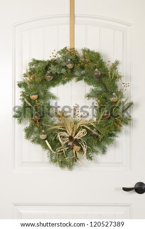 A Christmas wreath on a white door with an agricultural theme