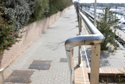 a chromo railing on a staircase, leading down to the harbor