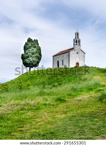 A church and a tree on a green hill