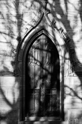 A church door with 'I heart cock' graffitied on it and shadows from tree branches across it.
