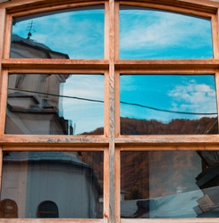 A church is reflected in the glass of the window. Blue sky with clouds. Distorted reflection of the dome of a church in the glass of a wooden window