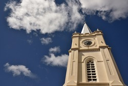 A church steeple against a deep blue sky with clouds