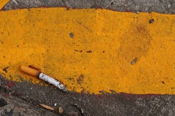 A cigarette butt/end - with long ash, on the dirty street. Concept of failure to quit smoking /cigarette butt tossers still a city cleaning issue