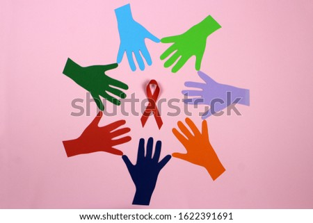 A circle of colored paper hands. AID, HIV red ribbon. Symbol of awareness, charity, support in disease, illness, ill. Medical health care, help and hope.