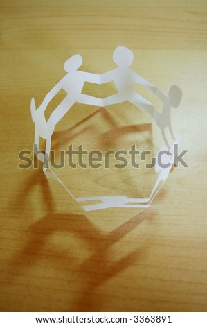 a circle of paper people representing team work