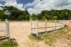 A circular fence to tame horses in a stud farm