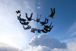 A circular group of skydivers is falling in the blue sky.