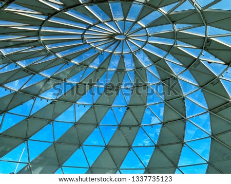 A circular mirror in a circular dome, shaped like a spiral with a bright sky background. Modern style interior is an energy-saving building due to the light from outside the glass. #1337735123