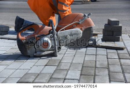 A circular saw with a rotating blade stands on paved paving slabs, building a road for pedestrians. Foto stock ©