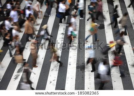 A city cross walk is littered with pedestrians.