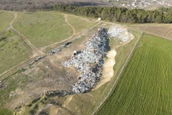 a city dump landfill located near the arable area. Aerial top view of a Huge Waste, garbage, dump landfill dump waste polluting products. Earth pollution and environmental disaster concept