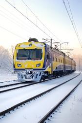 a city suburban train on snow covered tracks