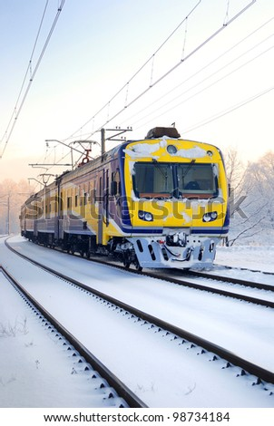 a city train on snow covered tracks