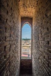 A city view through window in La Torre del Mangia, Piazza del Campo, Palazzo Pubblico. Siena, Italy.