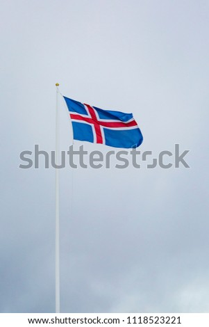 A civil flag and ensign Iceland against a clouded sky. The civil national flag of Icelanders is blue as the sky with a snow-white cross, and a fiery-red cross inside the white cross. #1118523221