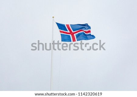 A civil flag and ensign Iceland against a clouded sky. The civil national flag of Icelanders is blue as the sky with a snow-white cross, and a fiery-red cross inside the white cross. #1142320619