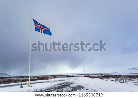 A civil flag and ensign Iceland against a clouded sky. The civil national flag of Icelanders is blue as the sky with a snow-white cross, and a fiery-red cross inside the white cross. #1165598719