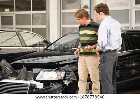 A claims adjuster showing the owner the damage done to the car after his assessment. He is holding a clipboard in his hand. Photo stock ©