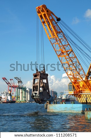 A clamshell dredger mounted on a barge in Kaohsiung port