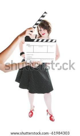 A clapper board being held up in front of a young actress dressed in pinup fashion.  Shot on white background.  Focus on actress.