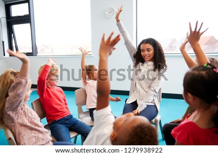 A class of infant school children sitting on chairs in a circle in the classroom, raising hands with their female teacher, close up
