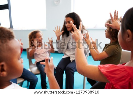 A class of infant school children sitting on chairs in a circle in the classroom, raising hands and learning to count with their female teacher, close up
