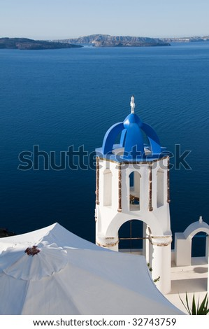 a classic blue dome church over the mediterranean sea harbor in oia ia  santorini with view of volcanic island in the cyclades greek islands