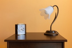 A classic flower-shaped lamp and an alarm clock on a wooden nightstand