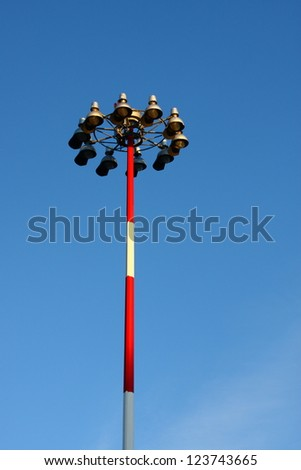 A classic old light pole with red and white stripes under Blue skies