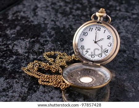 a classic pocket watch on velvet background - stock photo