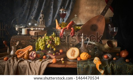 A classic still-life in the Dutch old masters style with lobster, fruits on a silver, platter, silver carafe.  old books , glass of wine, hunting horn and guitar lute .