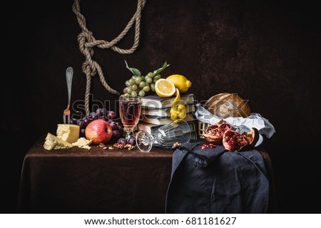 A classic still-life in the Dutch style with fruit cheese and books. On a dark brown background. With draperies #681181627