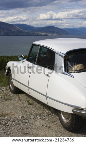 A classic, streamlined, white French car is parked overlooking a lake.