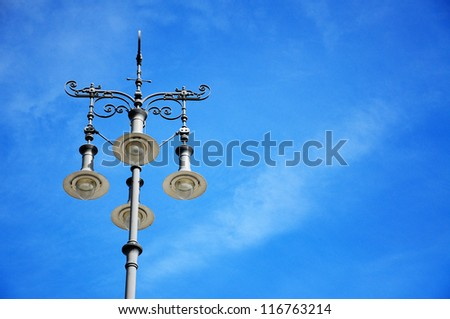 A classic street light against blue sky.