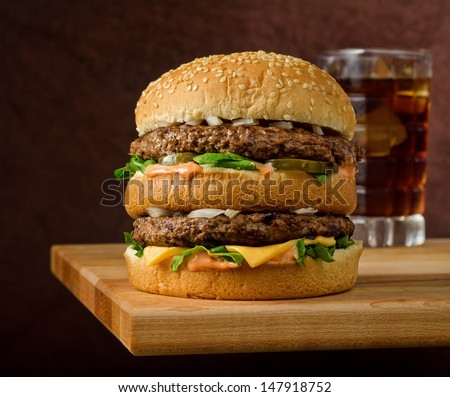 A classic style double cheeseburger with two beef patties sauce lettuce cheese pickles and onions on a sesame seed bun with soda