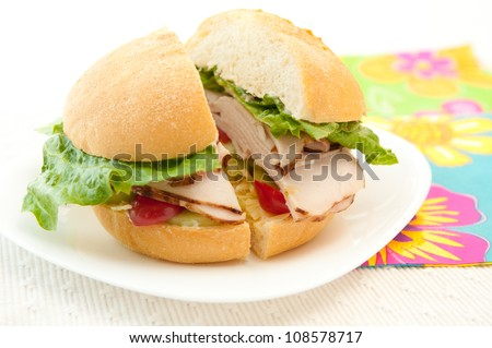 a classic turkey sandwich on a calabrese roll with tomato, lettuce, cheese, cucumber and mayonaise. A lunchtime favorite