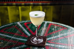 A classic yellow sour cocktail with foam in a nick and nora glass with lime zest garnish