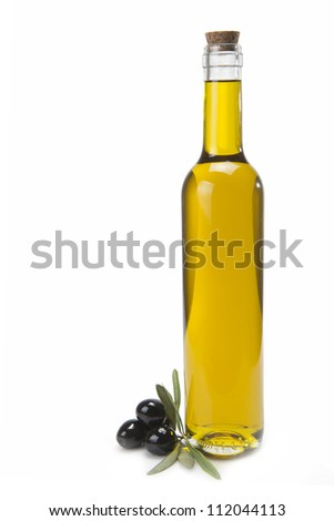 A classical glass bottle of olive oil and some black olives isolated over a white background