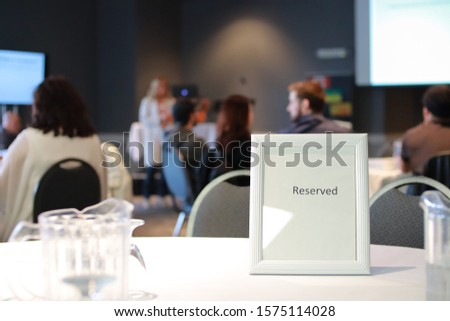 A Classy reserved table sign with a water drinking glass at a business event for entrepreneurs. There is shallow depth of field in photo. #1575114028