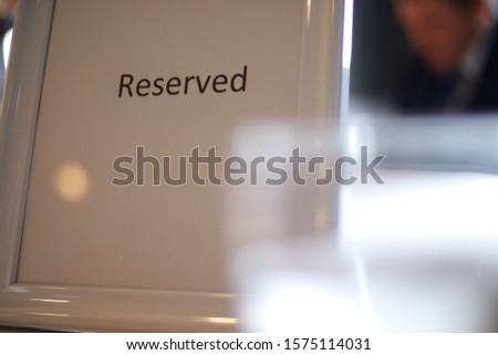 A Classy reserved table sign with a water drinking glass at a business event for entrepreneurs. There is shallow depth of field in photo. #1575114031