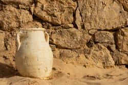 A clay jug stands in the sand againA clay jug stands in the sand against a stone wallst a stone wall