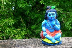 a clay model of Indian god Krishna , with trees in background