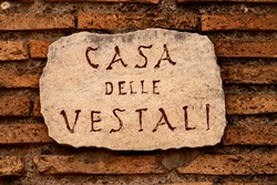 A clay street sign in Rome translated as 'Street of the Vestals'