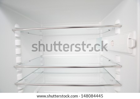 A clean and empty refrigerator with white walls and glass shelves. No products inside.