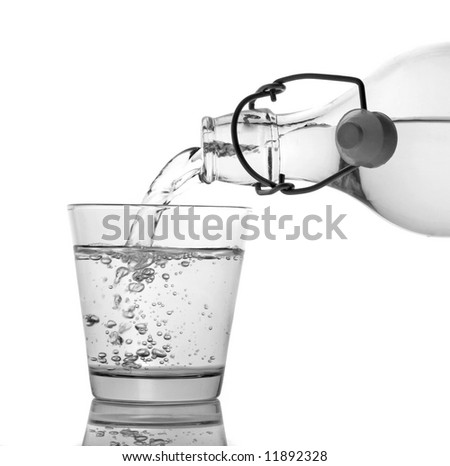 A clean glass of water being served from a bottle isolated on white