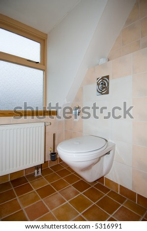 A clean, modern toilet in a tiled bathroom