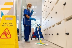 A cleaner with a mask on her face cleans the floor with the mop.Caution wet floor sign close up